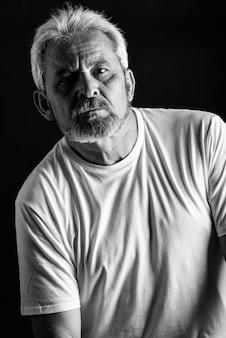 Poważny dojrzały mężczyzna z białymi włosami i brodą