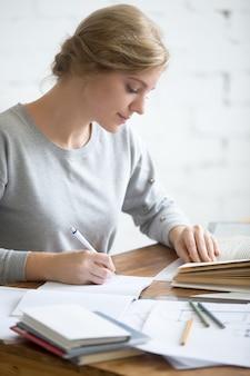 Profil portait dziewczyny wykonującej zadanie pisemne w książce