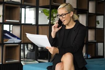 Przekonana, bizneswoman omawianie dokumentów na telefon