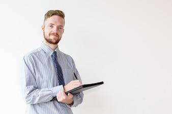 Przekonany, młody biznesmen z folderu i długopis
