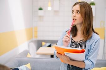 Przemyślana dziewczyna stojąca z notebookiem