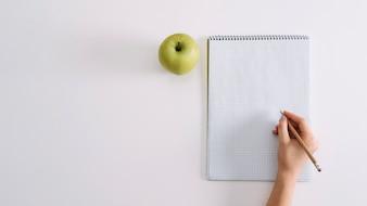 Przycinaj student z notatnikiem i jabłkiem