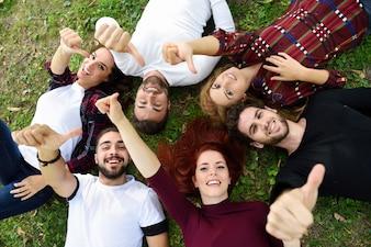 Przyjaciele z kciuki i uśmiechnięte, leżąc na trawniku