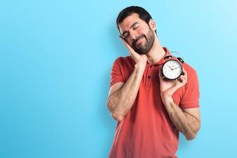 Przystojny mężczyzna trzyma zegar vintage na kolorowym tle