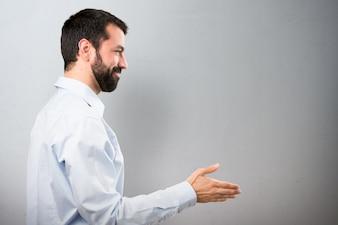 Przystojny mężczyzna z brodą czyniąc ofertę na teksturowanej tle