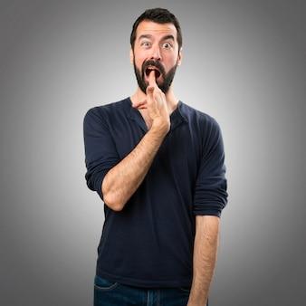 Przystojny mężczyzna z brodą dokonywania gest samobójstwo na szarym tle