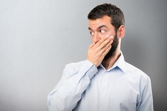 Przystojny mężczyzna z brodą obejmujące usta na teksturowanej tle