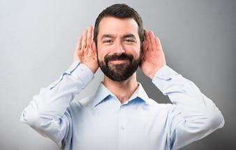 Przystojny mężczyzna z brodą słuchania coś na teksturowanej tle