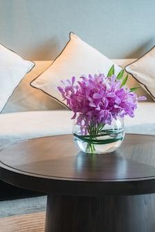 Purpurowe kwiaty na szklanym wazonie