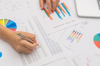 Ręka kobiety biznesu z wykresów finansowych i laptopa na TA