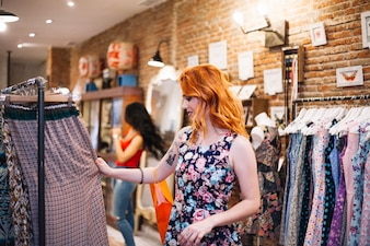 Red-Haired kobieta wybierając sukienkę