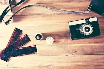 Retro zabytkowe aparatu fotograficznego i filmu fotograficznego na drewnianym tle