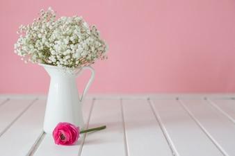 Różowy kwiat obok ozdobnym wazonie