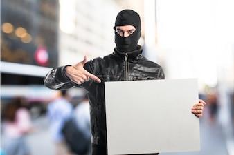 Robber trzyma puste plakietkę na tle nieostry