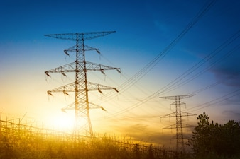 Słońce ustawione za sylwetką słupów elektrycznych