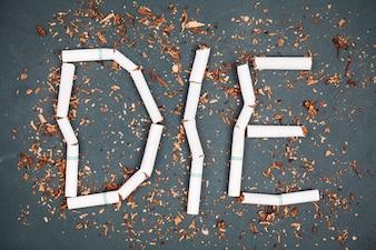 Słowa DIE na znak zakaz palenia wykonane z łamanych papierosów i tytoniu na tablicy.