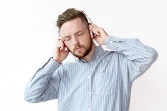 Skoncentrowany człowiek słuchania muzyki w słuchawkach