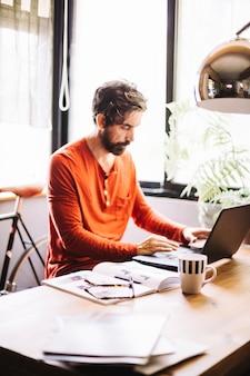 Skoncentrowany pracownik płci męskiej w stylowym biurze