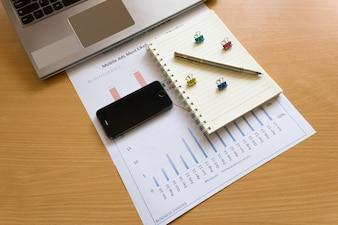 Smartphone w dłoni na drewnianym stole z laptopem. analiza wykresów