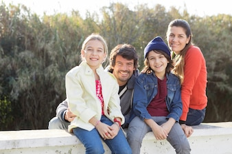 Smiling rodzeństwo siedzi z rodzicami