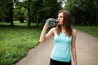 Sportsmenka w parku picia wody butelkę