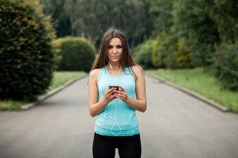 Sportsmenka z telefonem komórkowym i zestawem słuchawkowym
