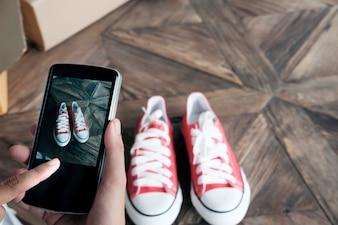 Sprzedający online korzysta z telefonu komórkowego, robienia zdjęcia produktu do przesłania do serwisu internetowego sklepu internetowego.
