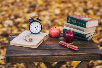 Stare książki, jabłka, opadłe liście, ołówki, zegary, dekoracje