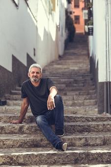 Starsza człowiek siedzi na schodach w tle miejskim