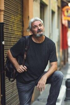 Starsza człowiek turystyczny z podróży plecak w tle miejskich.