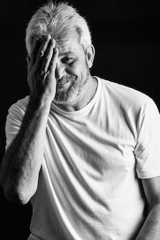 Starsza człowiek z białymi włosami i brodą uśmiecha się