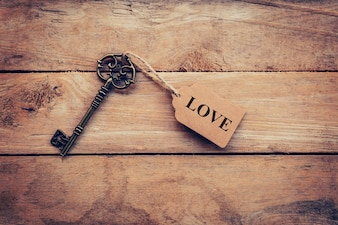 Stary klucz zabytkowe i znacznik tekstu LOVE na tle drewna.
