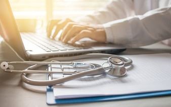 Stetoskop na recepty schowka i lekarz pracuje na laptopie na biurko w szpitalu, koncepcja opieki zdrowotnej i medyczne, vintage kolor, selektywne focus