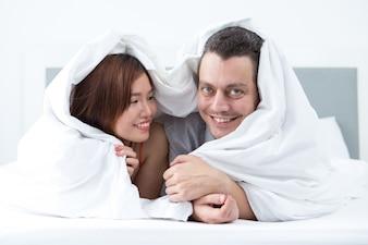 Szczęśliwa para owinięta w koc w łóżku