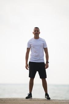 Szczęśliwy młody człowiek w odzieży sportowej uśmiecha się do kamery