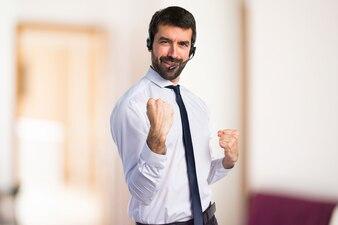 Szczęśliwy młody człowiek z zestawem słuchawkowym na tle unfocused