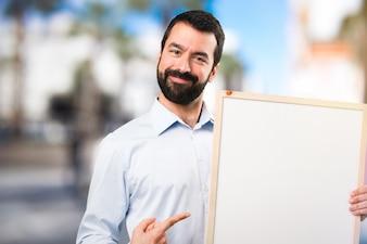 Szczęśliwy przystojny mężczyzna z brodą trzyma puste plakietkę na tle unfocused
