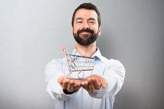 Szczęśliwy przystojny mężczyzna z brodą trzyma zabawkę koszyka supermarketów na teksturowanej tle