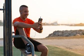 Szczęśliwy sportowiec słuchania muzyki z telefonu komórkowego