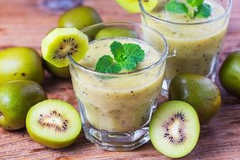Szklankę soku kiwi ze świeżych owoców na drewnianym stole