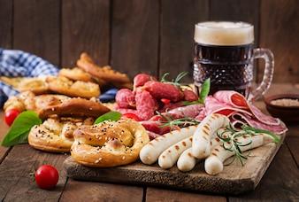 Szklanka piwa, precel i różnych kiełbas na drewnianym tle. Oktoberfest.