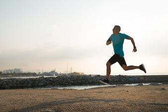 Szybki biegacz trenuje sam na plaży