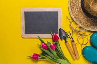 Tablica i narzędzia ogrodnicze na żółtym tle