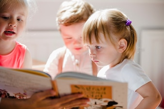 Toddlers czyta książkę w przedszkolu
