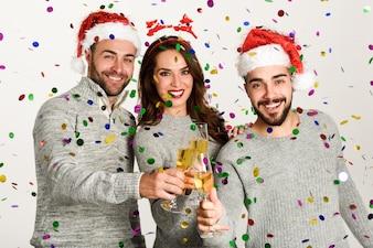 Trzech młodych ludzi opiekania z szampanem z Santa kapelusze na białym tle