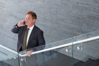 Uśmiecha się Mężczyzna rozmawia przez telefon na schodach