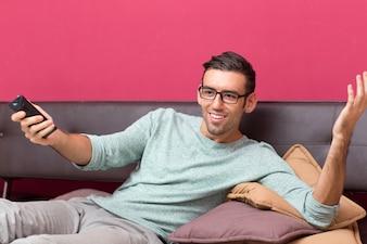 Uśmiechnięta Człowiek ogląda interesujące Program w telewizji