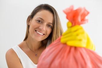 Uśmiechnięta kobieta podając pełną torbę na śmieci