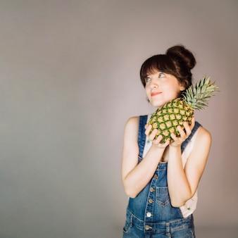 Uśmiechnięta kobieta z ananasem