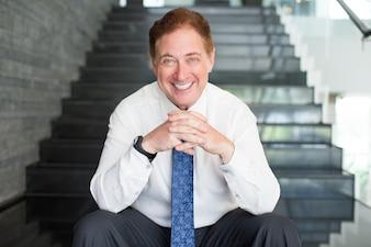 Uśmiechnięta wyższych biznesmen siedzi na schodach